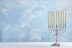 Hanukkah menorah on table. Against color background royalty free stock images