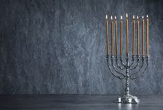 Hanukkah menorah on table. Against grey background stock images