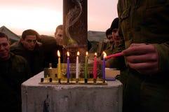 Hanukkah - soldados israelitas que iluminam um Chanukiah imagens de stock