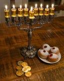 Hanukkah table. Lighting hanukkah candles with sufganiya and hanuka coins Royalty Free Stock Photography
