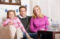 Hanukkah:. A young family celebrating Hanukkah at home, with presents, reading, dreidels, etc stock image