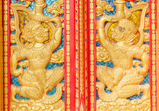 The hanuman golden carved on red door in buddhism temple. The hanuman golden carved on red door in buddhism public temple stock image