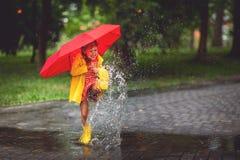 Hap a menina feliz da criança com um guarda-chuva e umas botas de borracha na poça fotos de stock
