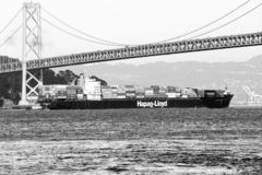 Hapag-Lloyd container ship moving under  Oakland Bay Bridge royalty free stock images