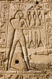 Hapi, God of the Nile. Stone carving of the Ancient Egyptian god of the River Nile Hapi.  Shown wearing a crown of lotus flowers.  Wall of the Temple of Seti I Stock Photos
