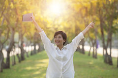Hapiness face of yonger woman and student book in hand standing. In summer park Royalty Free Stock Image