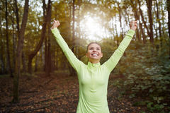 Hapiness from good work. Portrait of happy sportswoman raising hands in victory gesture and looking up Stock Images