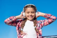 Hapiness verdadeiro Fan de música pequeno Menina pequena feliz A menina pequena escuta a música exterior Fones de ouvido felizes  fotografia de stock royalty free