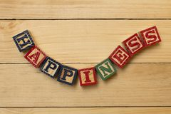 Hapiness wood cube words on wooden table cool Royalty Free Stock Photo