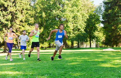 Happ young sportsmen racing wit badge numbers. Fitness, sport, friendship, race and healthy lifestyle concept - group of happy teenage friends or sportsmen Stock Photography