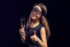 Happe kobieta w maskowy trzymać szklany z szampanem fotografia royalty free