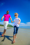 The happiest childhood: father and son running along the tropica Stock Photos