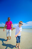The happiest childhood: father and son running along the tropica Stock Photo