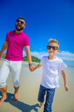 The happiest childhood: father and son running along the tropica Stock Photography