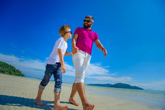 The happiest childhood: father and son walking along the tropica Stock Photography