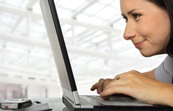 Happily into it. Close-up of a female working profoundly on a laptop, smiling royalty free stock image