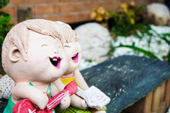 Happily Couple in The Garden. Couple ceramic doll playing guitar and sing a song in garden Royalty Free Stock Photo