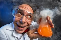 Happily crazy chemist with his experiment royalty free stock photos