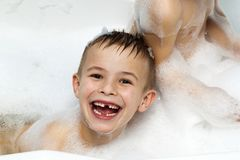 Happily laughing child boy taking a bath. Milk teeth missing Stock Images