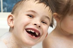 Happily laughing child boy taking a bath. Milk teeth missing Royalty Free Stock Photos