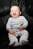 Happily Lauging Seated Baby Stock Images