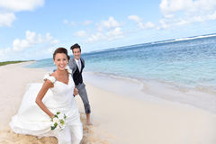 Happily married couple running on the sandy beach Stock Image