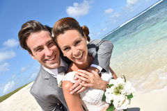 Happily married newly-weds on the beach smiling Stock Photo