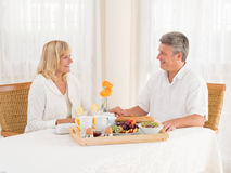 Happily mature senior married couple enjoy a healthy breakfast holding hands. Happily married mature couple enjoying a healthy breakfast sitting at the table Royalty Free Stock Photos