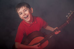 Singing boy with acoustic guitar Stock Image