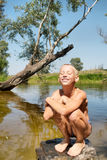 Happily smiling boy sitting on rock in lake Royalty Free Stock Photography