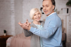 Happily smiling and dancing senior couple royalty free stock photography