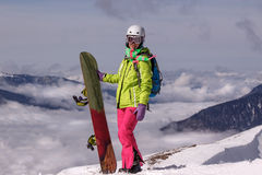 Happily smiling girl snowboarder in winter mountains. Above the clouds Stock Photography