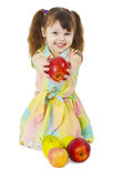 Happily smiling little girl gives an apple Royalty Free Stock Photo