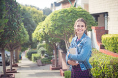 Happily smiling young successful woman with books in sunny stree Royalty Free Stock Images