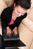 Happily working young business woman with laptop. Smiling young business woman working with laptop on her laps; sitting on a sofa in a lounge - top view royalty free stock images