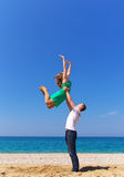 Happines. Lad raises girl high on hand skyward Stock Photo