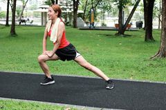 Happines Asian woman stretching her legs before run in park. Fitness and exercise concept. royalty free stock photo