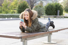 Happines beautiful girl with smart phone lying on the bench. Royalty Free Stock Photo