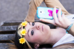 Happines beautiful girl with smart phone lying on the bench. Stock Image