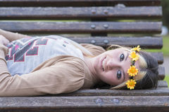 Happines beautiful girl with smart phone lying on the bench. Royalty Free Stock Image