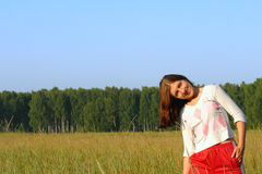 Happines girl in the field. The smiling girl standing in the field Royalty Free Stock Image