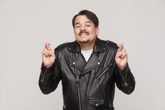 Happines man in black jacket toothy smiling and showing good luc Stock Photography