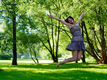 Happiness. Happy beautiful laughing woman jumping in the park in summer Royalty Free Stock Photography