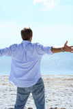 Happiness. Man lifting his arms out to sides looking at ocean Royalty Free Stock Photography
