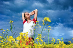Happiness. Pregnant young woman very happy in a field of rapeseed royalty free stock photo