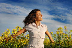Happiness. Young woman smiling happy in a field of rapeseed stock photography