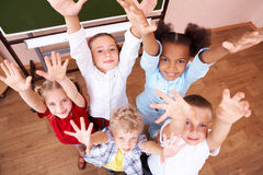 Happiness. Image of cute schoolchildren looking at camera and laughing with their arms raised Stock Photo
