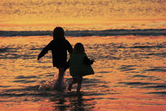 Happiness. Two kids in the see at sunset Royalty Free Stock Photo
