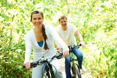 Happiness. Photo of happy husband and wife laughing while riding bicycles in park stock photos