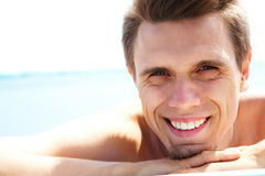 Happiness. Photo of smiling guy looking at camera while sunbathing Stock Photo